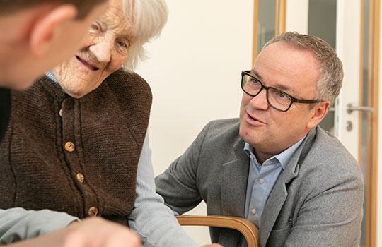 Leitungsperson spricht mit Seniorin
