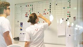 Pflegefachpersonen vor Whiteboard mit Belegungsplan