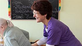 Pflegefachperson hilft Seniorin beim Hinsetzen